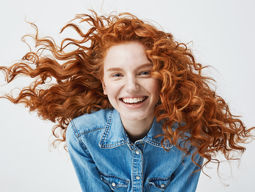 woman with red hair smiles with lingual braces