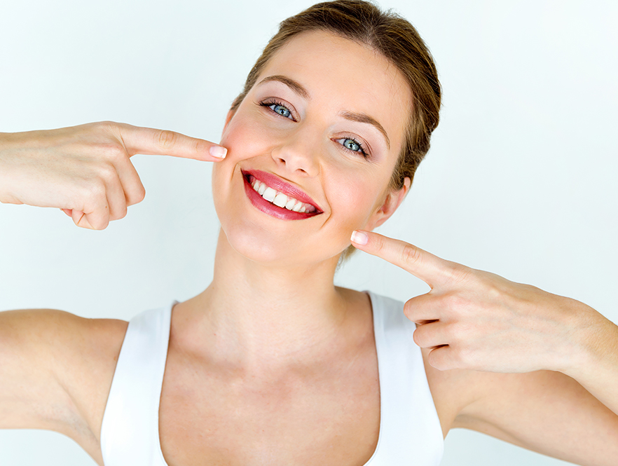 woman smiles and points at invisible braces behind the teeth
