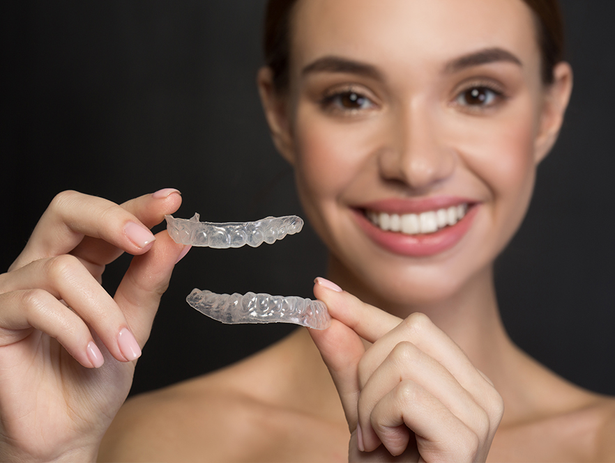 woman holds clear aligners in close up photo