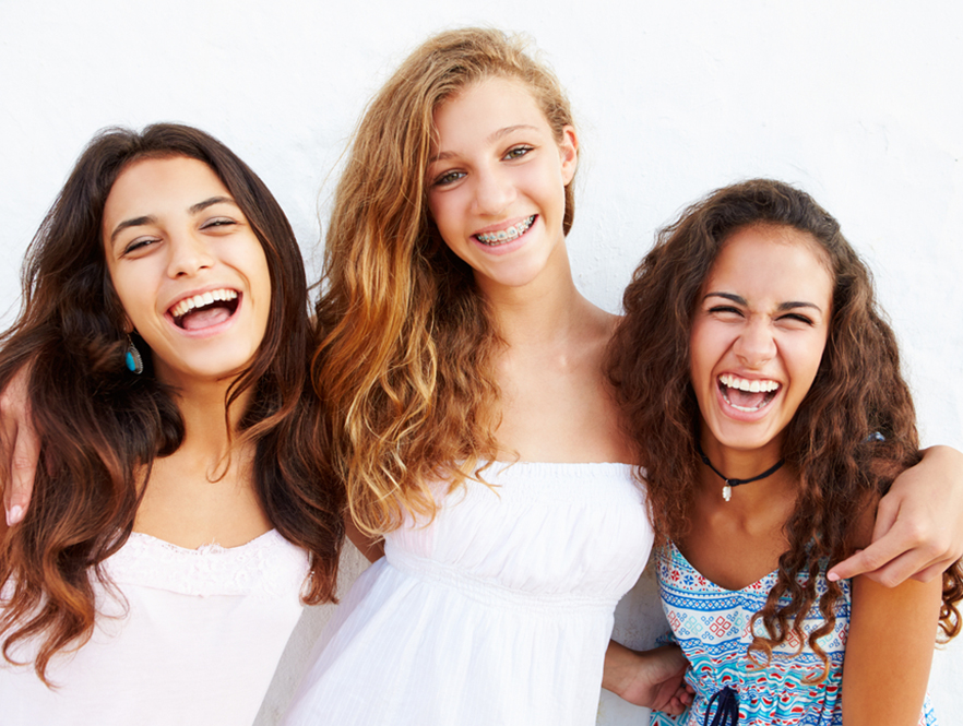 group of girls smiling, two eat before getting braces