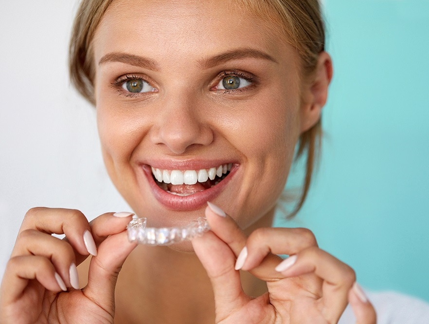 Smiling woman putting in clear aligner